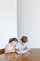 Boy (7-9) and girl (5-6) doing homework together