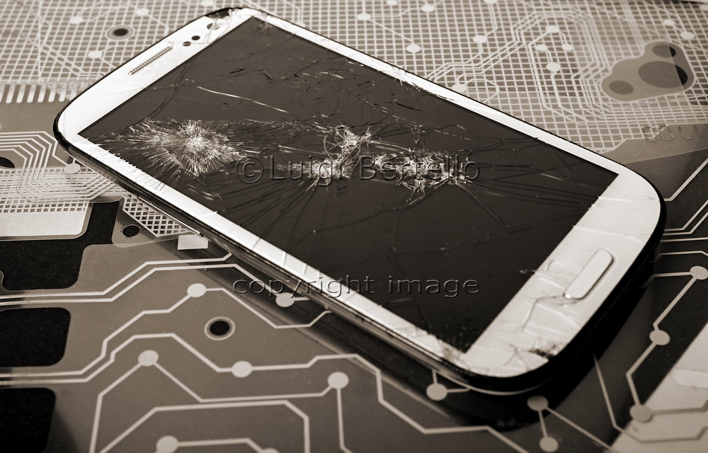 Phone with broken screen on the background of printed circuit board.