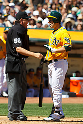 April 3, 2011; Oakland, CA, USA;  Oakland Athletics left fielder Josh Willingham (16) argues a called strike with MLB umpire Paul Emmel (50) during the first inning against the Seattle Mariners at Oakland-Alameda County Coliseum.