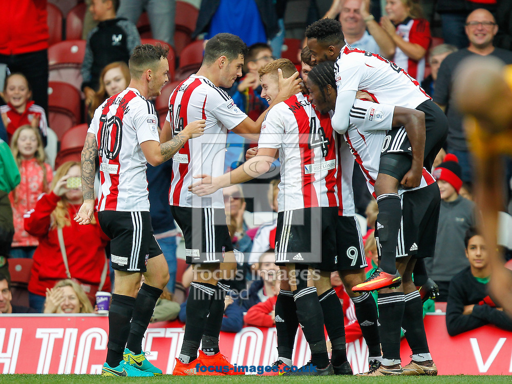 Scott Hogan of Brentford is congratulated by his team mates after scoring his third and Brentford's fifth goal during the Sky Bet Championship match between Brentford and Preston North End at Griffin Park, London<br /> Picture by Mark D Fuller/Focus Images Ltd +44 7774 216216<br /> 17/09/2016