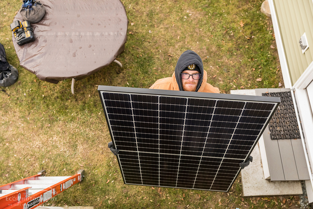 Revision Energy employee John Rawley, readies a solar panel during an installation on a single family home in Lowell, Massachuetts.