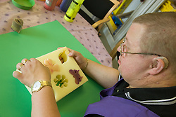 Day service user choosing a shape from a mould to use in painting activity,