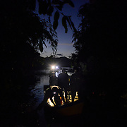 A boat ferrying honey hunters from their camp anchored at the edge of the forest during twilight.