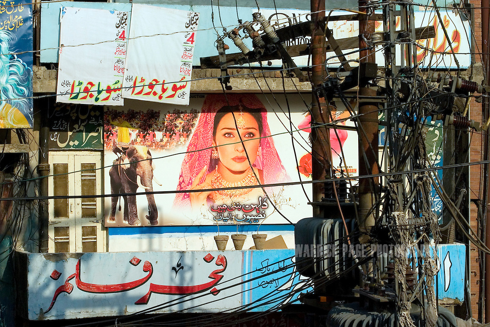 LAHORE, PAKISTAN - MAY 11: A street-scence in the film-poster painting district on Friday, May 11, 2007, in Lahore, Pakistan. Billboard painters have had to cut their prices in half due to few Lollywood productions and the use of soft-porn posters to entice patrons. As thawing relations between Pakistan and India lead them closer to regional stability, Pakistan's film industry takes another hit as Bollywood films dominate an already floundering institution, as the Pakistani government eases a 43-year-old ban on screening Indian films and audiences are drawn to their neighbours silver-screen theatrics. Once a thriving film industry in the chaotic and colourful city of Lahore, Pakistan's answer to Bollywood - Lollywood - is now a shadow of its former self. Two decades ago 11 studios averaged a collective 100+ films per year as cinemagoers filled more than 1000 theatres across the country. Today, only one functioning studio struggles to produce a single film for the country's 200 decaying theatres. (Photo by Warrick Page)