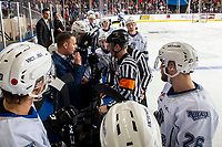 KELOWNA, BC - NOVEMBER 6:  Referee Brett Iverson stands at the boards and speaks to Victoria Royals' head coach Dan Price at the Kelowna Rockets at Prospera Place on November 6, 2019 in Kelowna, Canada. (Photo by Marissa Baecker/Shoot the Breeze)