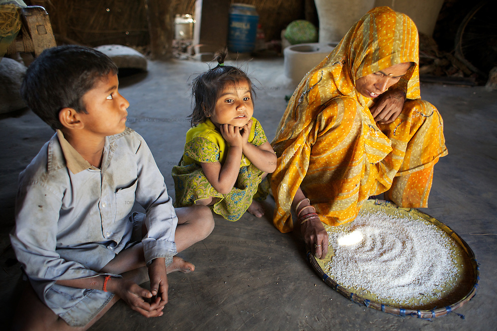 Shobha Devi cleans rice with two of her children Mannu (left), 7 and Sandhya, 5.  <br /> at home in their mud and thatch house. <br /> <br /> Shobha Devi, age 35, is from the from the ostracized Dalit Chamar caste. Shobha has four children, the eldest of whom - a daughter - is married. Shobha's husband has been working in Mumbai as a seasonal migrant for the past 25 years. He returns home for harvests and during the monsoon to help his family cope with the inevitable flooding that forces them to vacate their home an move to higher ground. The family own one bigha of land (1,300 sq metre) which is not enough to supper their nutritional needs so Shobha Devi - an occassionaly her children - also undertake agricultural labour on other people's land. Shobha is a member of the village SHG (Self Help Group).<br /> <br /> Ostracized, largely illiterate, ignored by an indifferent administration, without land adequate to support their families' needs, the Dalit residents of Kharihaniya village regularly suffer from hunger. The land around the village floods every monsoon season, destroying crops and forcing resident to vacate their homes and move to higher land. Without local opportunities for work, many of Kharihaniya's men have migrated, undertaking menial jobs in far off cities including Mumbai and Chennai. Only about 25% of those living in Kharihaniya village receive subsidized food as part of the PDS (Public Distribution System) even thought the circumstances of most would entitle them to such assistance. Intervention by Oxfam partners (Grameen Development Services) led to the establishing of a local SHG (Self Help Group) three years ago. The SHG allows women to save and borrow and invest in their farms while offering an opportunity to discuss problems and share ideas. Unlike the private money lenders that charged interest rates of 10%, women borrowing with an SHG only have to pay 2-3%.<br /> <br /> Photo: Tom Pietrasik<br /> Kharihaniya, Marajganj District, Uttar Prades