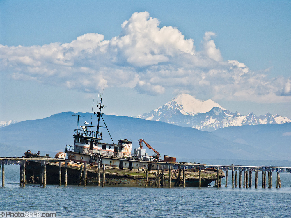 "Mount Baker (10,775 feet elevation) rises in the North Cascades 40 miles away from an old dock and rusting boat in Anacortes, on Fidalgo Island in Skagit County, Washington, USA. Anacortes is known for its Washington State Ferries terminal serving San Juan Islands, Guemes Island, and Victoria via Sidney, British Columbia. ""Anacortes"" is a consolidation of the name Anna Curtis, who was the wife of early Fidalgo Island settler Amos Bowman."