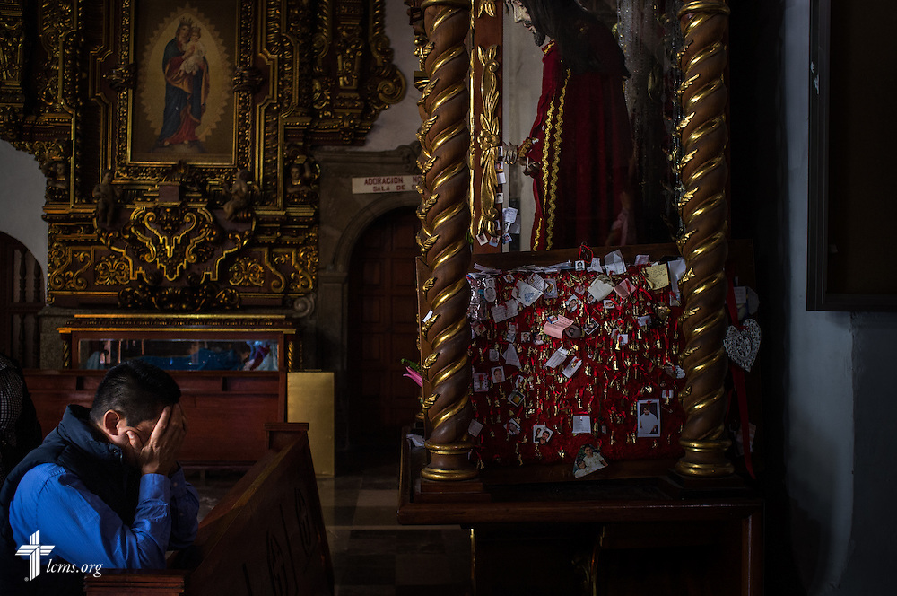 A man buries his hands as he kneels at a Catholic cathedral in Mexico City on Sunday, Jan. 15, 2017. Erik M. Lunsford