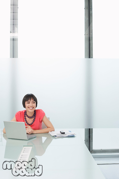 Woman using laptop in modern cubicle