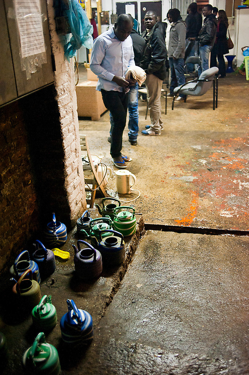 Afrikaanse migranten in gemeenschappelijke ruimte met sanitair. Sinds 2011 wonen 150 Afrikaanse migranten in een voormalige fabriek in de Parijse voorstand Montreuil, omdat ze illegaal in Frankrijk verblijven, kunnen ze geen woonruimte huren. In het 450 m2 grote pand wonen jonge mannen uit Malië, Ivoorkust, Bukina Faso, Niger.