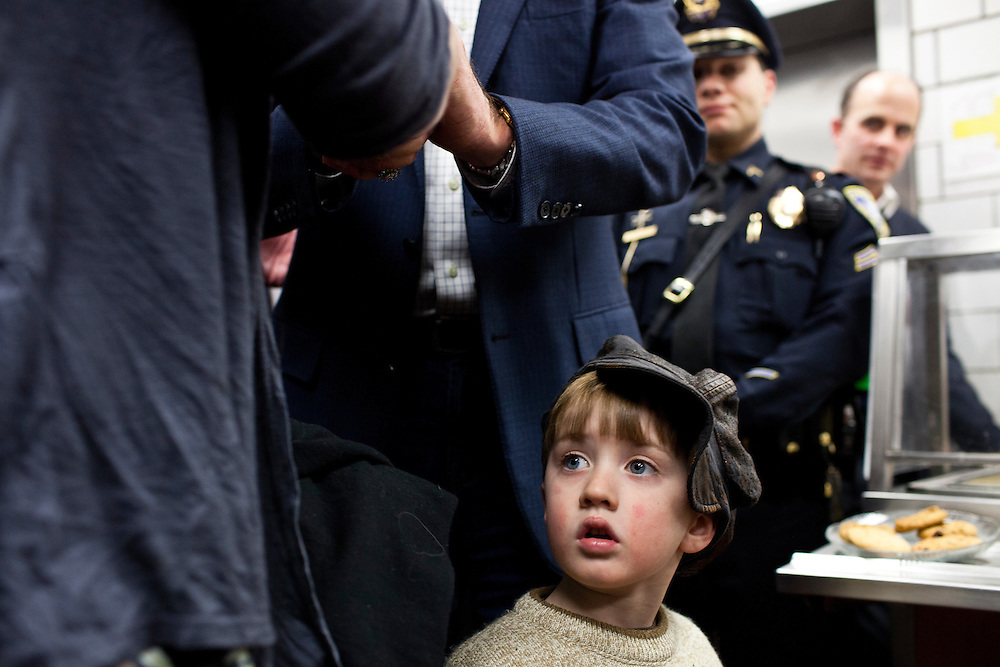 A young boy walks past as Republican presidential candidate Mitt Romney, behind him, shakes hands with guests at a spaghetti dinner on Friday, January 6, 2012 in Tilton, NH.