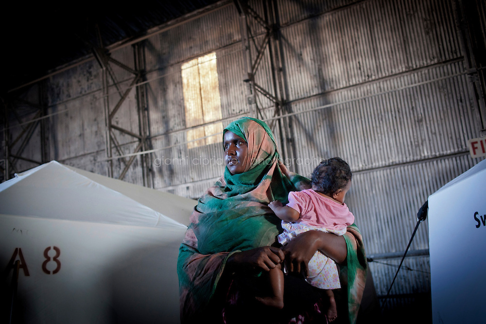 HAL FAR, MALTA - JUNE 21: A Shuka, a 25 years old immigrant from Somali, is here with her son by the Swiss Red Cross tents inside the Hangar Open Center in Hal Far (which translates as &quot;Rat's Town&quot;) on June 21, 2011. The Hangar Open Center is a field with an ex-aircraft hangar which includes Swiss Red Cross tents in a dark, non lit space, and external containers. The conditions are very poor and the has inflamable oil on the floor.<br /> <br /> The Open Centres in Malta serve as a temporary accomodation facility, but they ended becoming permanent accomodation centres, except for those immigrants who receive subsidiary protection or refugee status and that are sent to countries such as the United States, Germany, Poland, and others. All immigrants who enter in Malta illegally are detained. Upon arrival to Malta, irregular migrants and asylum seekers are sent to one of three dedicated immigration detention facilities. Once apprehended by the authorities, immigrants remain in detention even after they apply for refugee status. detention lasts as long as it takes for asylum claims to be determined. This usually takes months; asylum seekers often wait five to 10 months for their first interview with the Refugee Commissioner. Asylum seekers may be detained for up to 12 months: at this point, if their claim is still pending, they are released and transferred to an Open Center.<br /> <br /> <br /> Gianni Cipriano for The New York Times