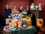 (MODEL RELEASED IMAGE). The Bainton family in the dining area of their living room in Collingbourne Ducis, Wiltshire, with a week's worth of food. Left to right: Mark Bainton, 44, Deb Bainton, 45 (petting Polo the dog), and sons Josh, 14, and Tadd, 12. Cooking methods: electric stove, microwave oven. Food preservation: refrigerator-freezer, a second small freezer. Favorite foods? Mark: avocado. Deb: prawn-mayonnaise sandwich. Josh: prawn cocktail. Tadd: chocolate fudge cake with cream. /// The Bainton family is one of the thirty families featured in the book Hungry Planet: What the World Eats (p. 140). Food expenditure for one week: $253.15 USD. (Please refer to Hungry Planet book p. 141 for the family's detailed food list.)
