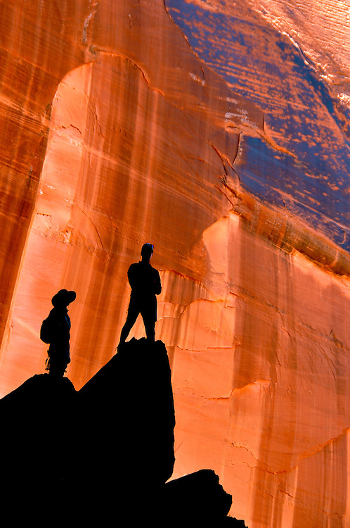 Hikers silhouetted against canyon wall in Arizona's Paria Canyon - Vermilion Cliffs Wilderness.