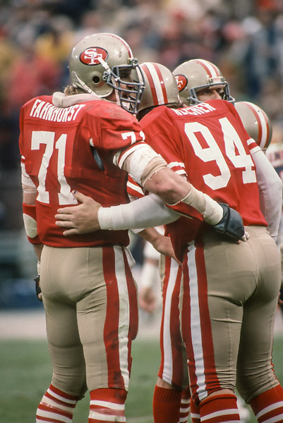 SAN FRANCISCO - JANUARY 6:  Keith Fahnhorst #71 and Louie Kelcher #94 of the San Francisco 49ers wait in the huddle for the play call by quarterback Joe Montana (visible behind) during the NFC Championship game against the Chicago Bears played on January 6, 1985 at Candlestick Park in San Francisco, California. (Photo by David Madison/Getty Images) *** Local Caption *** Keith Fahnhorst;Joe Montana