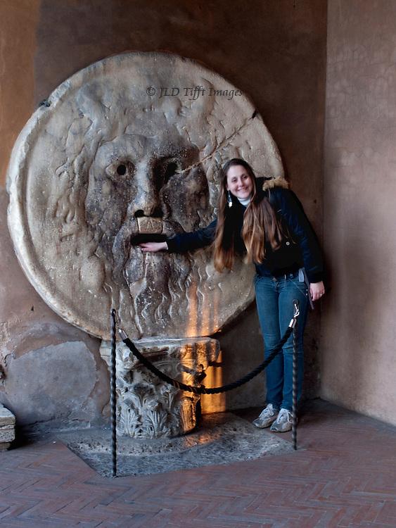 Bocca della verita, in the porch of Santa Maria de Cosmedin, Rome.  Young woman  smiling, her hand in the mouth of the figure.