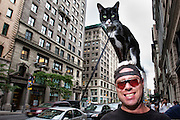 A man walks in downtown New York City with his cat on his head.