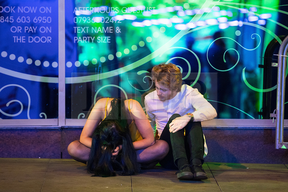 © Licensed to London News Pictures . 08/04/2017 . Manchester , UK . A woman sits on the pavement with her head in her hands as a man sits alongside her , on Withy Grove in Manchester City Centre . Greater Manchester Police have authorised dispersal powers and say they will ban people from the city centre for 48 hours , this evening (7th April 2017) , in order to tackle alcohol and spice abuse . Photo credit : Joel Goodman/LNP