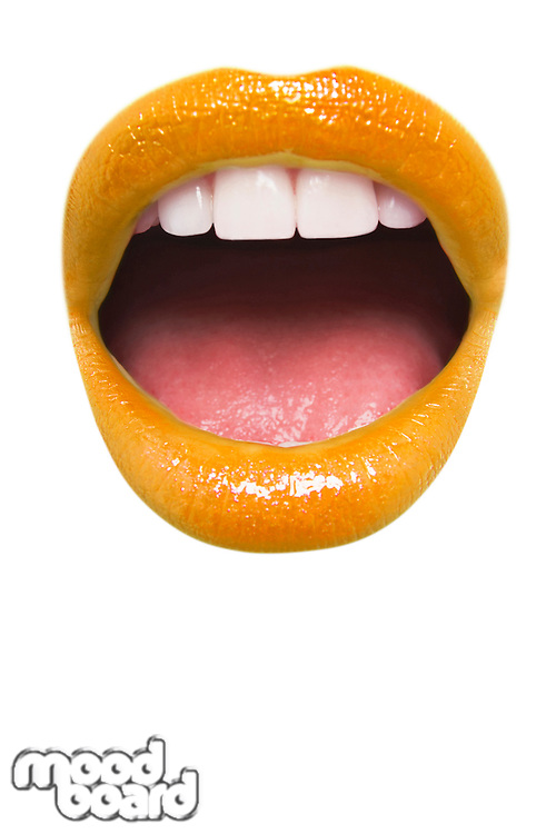 Close-up view of female wearing orange lipstick with mouth open over white background