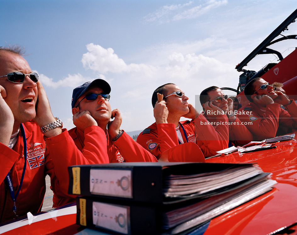 Pilots the 'Red Arrows', Britain's Royal Air Force aerobatic team block ears during pre-flight briefing before display..