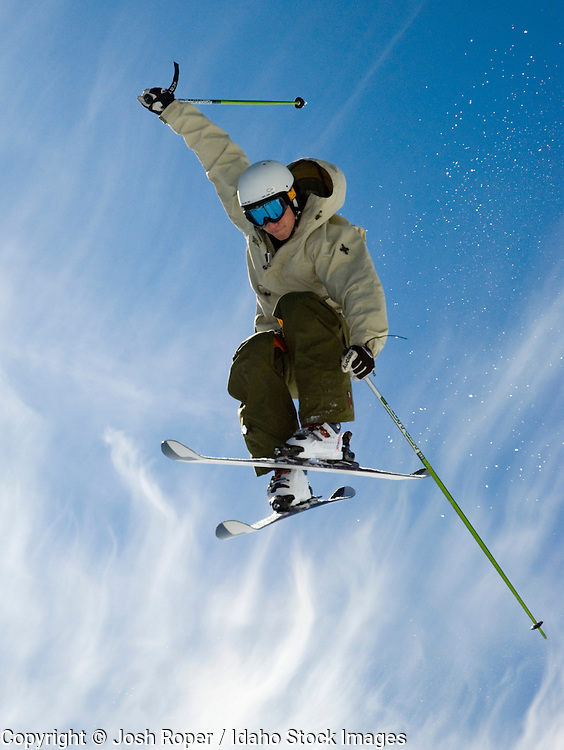 Idaho. A skier flies high on a beautiful blue sky day with dramatic clouds.