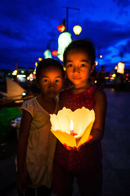 Young girls sell candled lanterns in the picturesqe ancient town of Hoi An, Vietnam.