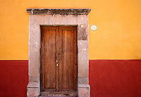 Red and yellow painted wall, wooden door, San Miguel de Allende Mexico