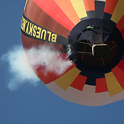 The hot air balloon of Lupercio Lima, Brazil, catches fire as he flies around rural Michigan near Battle Creek during competition in the 20th FAI World Hot Air Ballooning Championships. Lima managed to put the fire out and land his balloon safely. Battle Creek, Michigan, USA. 23rd August 2012. Photo Tim Clayton