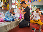 "05 APRIL 2015 - CHIANG MAI, CHIANG MAI, THAILAND:  A Tai Yai boy being ordained as a Buddhist novice prays with members of his family during the second day of the three day long Poi Song Long Festival in Chiang Mai. The Poi Sang Long Festival (also called Poy Sang Long) is an ordination ceremony for Tai (also and commonly called Shan, though they prefer Tai) boys in the Shan State of Myanmar (Burma) and in Shan communities in western Thailand. Most Tai boys go into the monastery as novice monks at some point between the ages of seven and fourteen. This year seven boys were ordained at the Poi Sang Long ceremony at Wat Pa Pao in Chiang Mai. Poy Song Long is Tai (Shan) for ""Festival of the Jewel (or Crystal) Sons.   PHOTO BY JACK KURTZ"