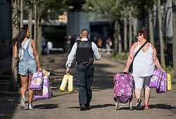 © Licensed to London News Pictures. 15/06/2017. London, UK. A policeman helps residents carry donated nappies the  day after the a huge fire at the Grenfell tower block in west London. The blaze engulfed the 27-storey building killing 12  - with 34 people still in hospital, 18 of whom are in critical condition. The fire brigade say that they don't expect to find anyone else alive.  Photo credit: London News Pictures