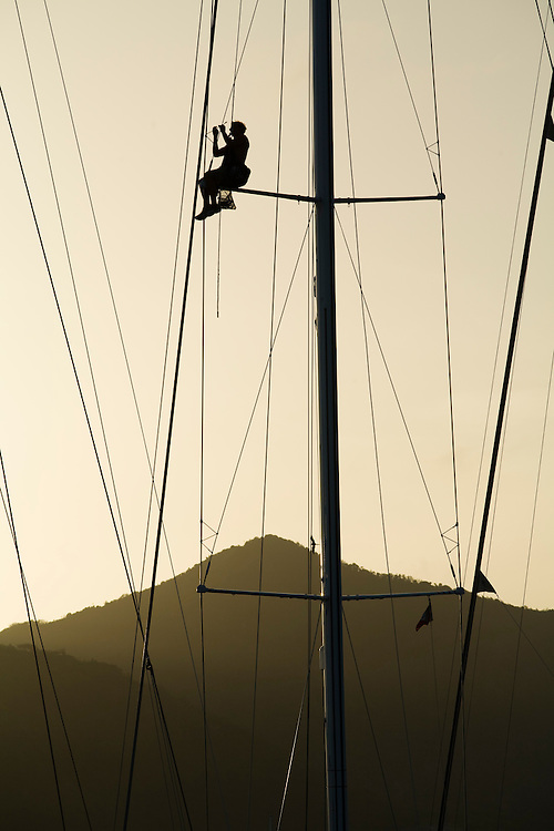 A crew member works aloft in the rigging , inspecting and repairing in preparation for the 2008 Antigua Sailing Week.This race is one of the worlds most prestigious  yacht races. It takes place annually off the cost of Antigua in the British West Indies. Antigua is a yachting haven, historically a British navy base in the times of Nelson.