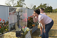 """East Meadow, New York, U.S. 11th September 2013. A woman and young girl study a Battlefield Cross display at the Global War on Terror """"Wall of Remembrance"""" a traveling memorial on display in New York for the first time, at Eisenhower Park on the 12th Anniversary of the terrorist attacks of 9/11. The unique 94 feet long by 6 feet high wall has, on one side, almost 11,000 names of those lost on September 11, 2001, along with heroes and veterans who lost their lives defending freedom of Americans over past 30 years. On the wall's other side is a timeline, with photos, covering 1983 to present day."""