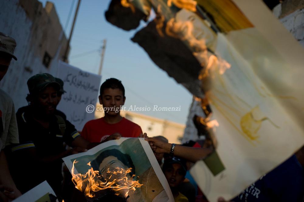 LIBYAN ARAB JAMAHIRIYA, Zintan : Libyan demonstrators burn pictures of embattled Libyan leader Kadhafi on the central square of Zintan during a gathering July 10, 2011.ALESSIO ROMENZI