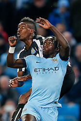 Bacary Sagna of Manchester City and Sammy Ameobi of Newcastle United compete in the air - Photo mandatory by-line: Rogan Thomson/JMP - 07966 386802 - 29/10/2014 - SPORT - FOOTBALL - Manchester, England - Etihad Stadium - Manchester City v Newcastle United - Capital One Cup Fourth Round.