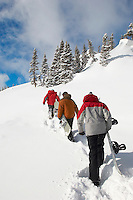 Three teenagers (16-17) holding snowboards hiking through snow rear view.