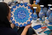Iran, Isfahan, 29.08.2016: Junge Frauen bemalen Teller und Vasen mit Ornamenten und Kalligraphie, Minakari, Basar in Isfahan. Mina-Kari ist die Kunst brillante Farben und Ornamente in aufwendiger Arbeit auf eine Kupferfläche zu bringen. Provinz Isfahan, Esfahan, Zentral-Iran.