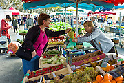 French woman buying grapes at fruit stall in food market at Esplanade  des Quais in La Reole, Bordeaux region, France
