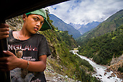 A young Nepali boy hangs onto the side of a jeep as it drives up a steep Himilayan mountain valley.