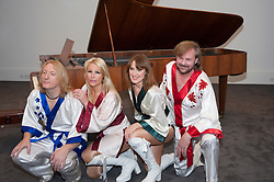 """© Licensed to London News Pictures. 27/08/2015. London, UK. Members of ABBA tribute band, Björn Again, perform at the photocall at Sotheby's for the upcoming auction of the """"ABBA piano"""", the instrument on which ABBA recorded their most celebrated songs including """"Mamma Mia"""", """"Waterloo"""" and """"Dancing Queen"""".  Estimated at £600,000-800,000, the piano will be part of Sotheby's Rock and Pop auction on 29 September. Photo credit : Stephen Chung/LNP"""