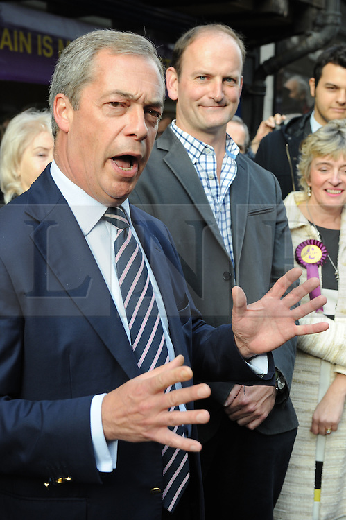 © Licensed to London News Pictures. 11/10/2014<br /> UKIP MP Douglas Carswell (back)  Nigel Farage talking in Rochester,Kent outside UKIP shop 30 Rochester High Street. <br /> UKIP Leader Nigel Farage  in Rochester today (11.10.2014)with Mark Reckless and new UKIP MP for Clacton Carswell.<br /> (Byline:Grant Falvey/LNP)