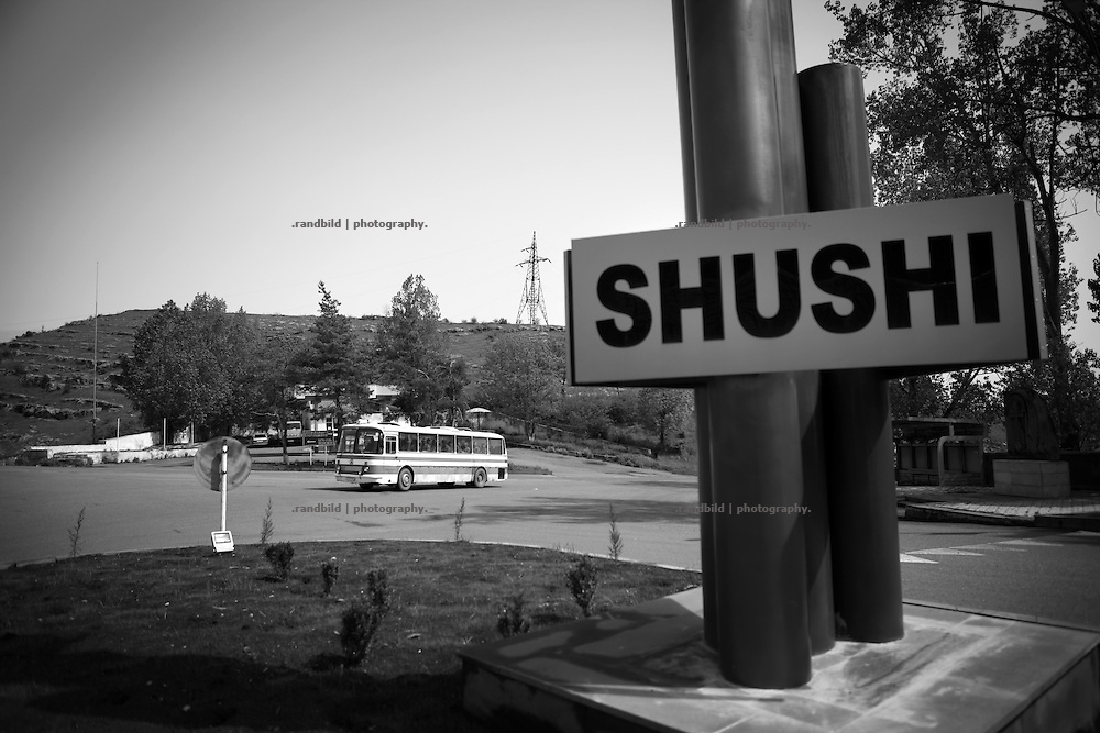"""Shushi sign at town entrance. This image is part of the photoproject """"The Twentieth Spring"""", a portrait of caucasian town Shushi 20 years after its so called """"Liberation"""" by armenian fighters. In its more than two centuries old history Shushi was ruled by different powers like armeniens, persians, russian or aseris. In 1991 a fierce battle for Karabakhs independence from Azerbaijan began. During the breakdown of Sowjet Union armenians didn´t want to stay within the Republic of Azerbaijan anymore. 1992 armenians manage to takeover """"ancient armenian Shushi"""" and pushed out remained aseris forces which had operate a rocket base there. Since then Shushi became an """"armenian town"""" again. Today, 20 yeras after statement of Karabakhs independence Shushi tries to find it´s opportunities for it´s future. The less populated town is still affected by devastation and ruins by it´s violent history. Life is mostly a daily struggle for the inhabitants to get expenses covered, caused by a lack of jobs and almost no perspective for a sustainable economic development. Shushi depends on donations by diaspora armenians. On the other hand those donations have made it possible to rebuild a cultural centre, recover new asphalt roads and other infrastructure. 20 years after Shushis fall into armenian hands Babies get born and people won´t never be under aseris rule again. The bloody early 1990´s civil war has moved into the trenches of the frontline 20 kilometer away from Shushi where it stuck since 1994. The karabakh conflict is still not solved and could turn to an open war every day. Nonetheless life goes on on the south caucasian rocky tip above mountainious region of Karabakh where Shushi enthrones ever since centuries."""