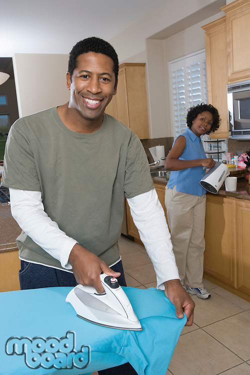 Mid-adult couple at domestic kitchen, man ironing