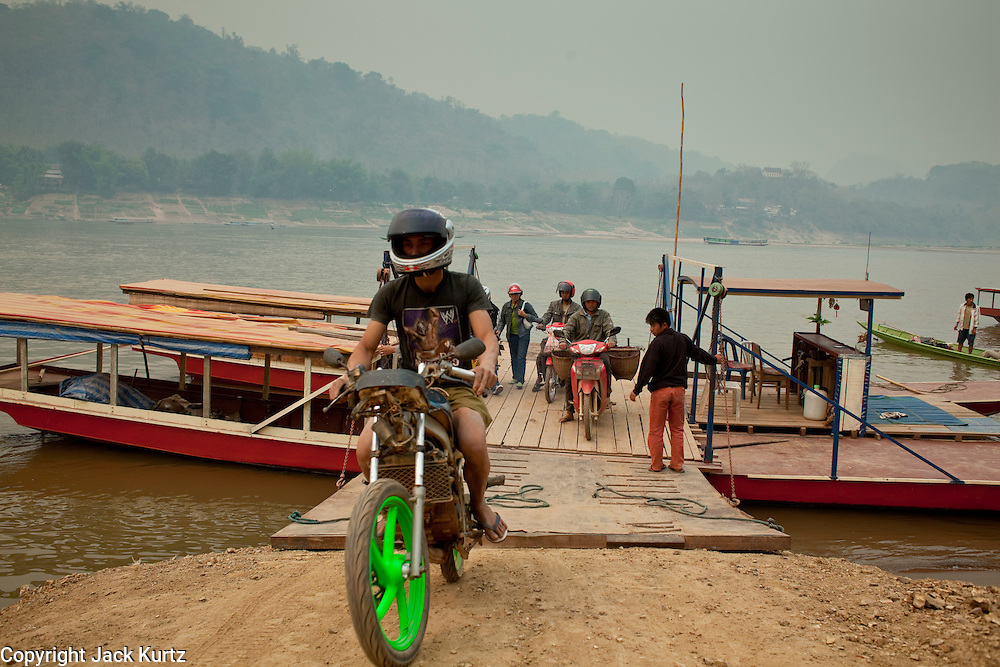 Mar. 15, 2009 -- LUANG PRABANG, LAOS: A man rides his motorcycle off of a jerry rigged car ferry across the Mekong River in Luang Prabang, Laos. The Mekong is the artery of Laos and slices the country into east and west but there are few bridges across the river so most people cross on boats.  Photo by Jack Kurtz