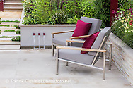 Detail of a pair of grey padded stainless steel chairs with teak arms and burgundy cushions which echo the colour of the uprights of the pergola under which they sit