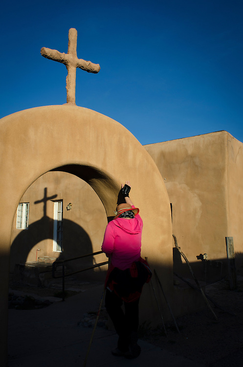 "Rose Marie Swanson prays at the courtyard entrance of El Santuario de Chimayo, Thursday, April17, 2014, having made the pilgrimage north from Santa Fe earlier that day. Pilgrims may take a small amount of Holy Dirt, believed to have healing powers, from ""el pocito"" or ""the little well"" inside El Santuario. (AP Photo/Jeremy Wade Shockley)"