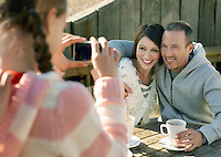 Pre teen girl photographing parents sitting at outdoor table