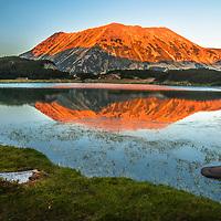 Massive mountain peak above a lake at sunset time