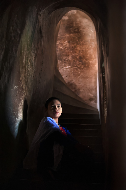 A woman at sunrise lit by a window in a temple at Bagan, Myanmar.