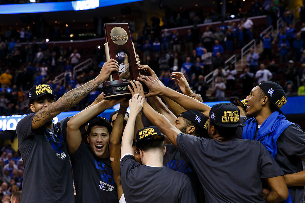 Mar 28, 2015; Cleveland, OH, USA; Kentucky Wildcats players lift up the trophy after defeating Notre Dame Fighting Irish in the finals of the midwest regional of the 2015 NCAA Tournament at Quicken Loans Arena. Mandatory Credit: Rick Osentoski-USA TODAY Sports
