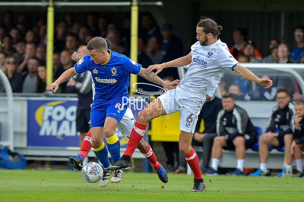 AFC Wimbledon Forward, Cody McDonald (10) and Portsmouth Defender, Christian Burgess (6) during the EFL Sky Bet League 1 match between AFC Wimbledon and Portsmouth at the Cherry Red Records Stadium, Kingston, England on 9 September 2017. Photo by Adam Rivers.